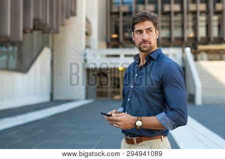 Man using smartphone outdoor. Portrait of young businessman using mobile phone while looking away on the street. Thoughtful business man in blue formal clothing using cellphone outside office building