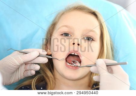 Little Baby Girl Sitting At Dental Chair With Open Mouth And Feeling Fear During Oral Check Up While