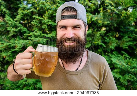 Alcohol and bar concept. Creative young brewer. Craft beer is young, urban and fashionable. Distinct beer culture. Hipster brutal bearded man hold mug cold fresh beer. Man enjoying beer in summer poster