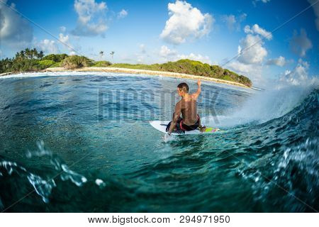 Surfer rides the ocean wave at sunset. Honkeys surf spot in the Maldives