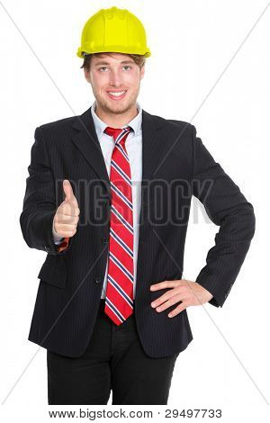 Engineer or architect showing thumbs up success hand sign in suit and construction work protection helmet hat isolated on white background. Young happy successful male professional.