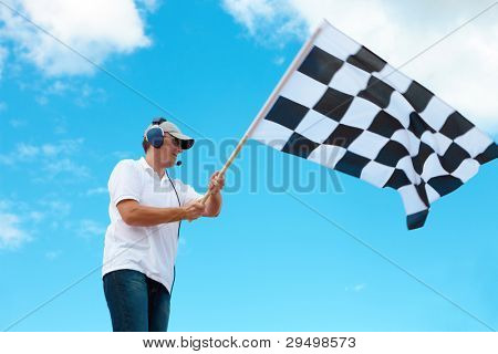 Man with headset holding and waving a checkered flag on a raceway poster