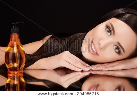 Beautiful Model On Black Glass With Hair Oil