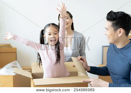 Happy Asian Family Playing With Cardboard Box In Their New Hous.having Fun Together At Moving Day. M