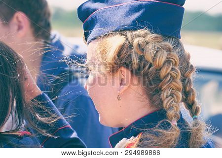 Woman with pigtails in uniform in a forage-cap. Rear view poster