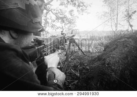 Hidden Re-enactor Dressed As German Wehrmacht Infantry Soldier In World War Ii Aiming A Machine Gun