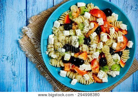 Greek Salad With Fresh Vegetables, Feta Cheese, Pasta And Black Olives On Blue Wooden Background Top