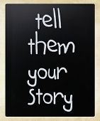 """Tell them your story"" handwritten with white chalk on a blackboard poster"