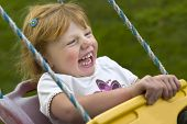 A young girl on a playground swing. poster