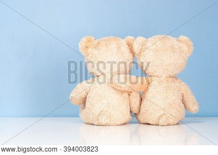 Two Teddy Bear Sitting On A White Table And Blue Background.