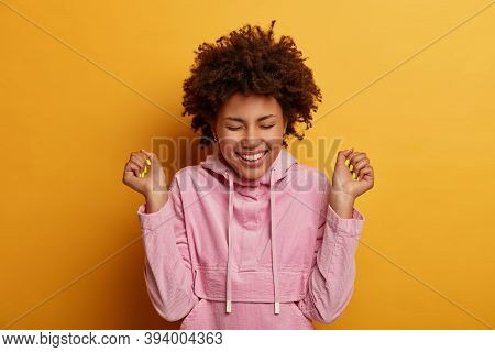 Portrait Of Empowered Relieved Woman With Curly Hair Makes Fist Bump Smiles From Happiness And Rejoi