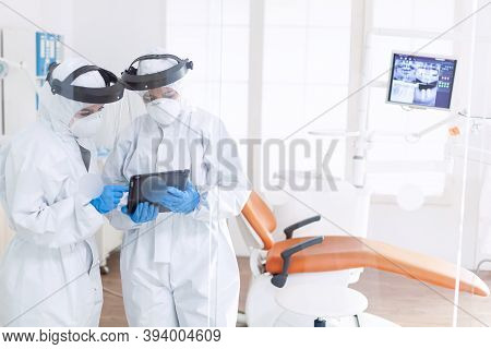 Dentist And Nurse During Covid-19 Outbreak In Ppe Suit Usint Tablet Pc. Stomatology Team In Dental O