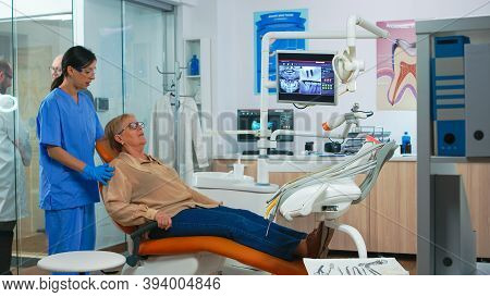 Nurse Inviting Senior Woman In Consultation Dental Room While Doctor Speaking With Patient. Assistan