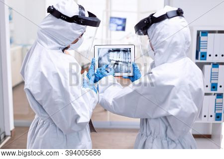 Dentistiry Team In Ppe Suit Holding Tablet With Teeth Digital Xray. Medical Specialist Wearing Prote
