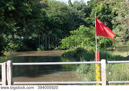 Red Flag And Yellow Water Level Indicator In River To Warn People Of Flooding