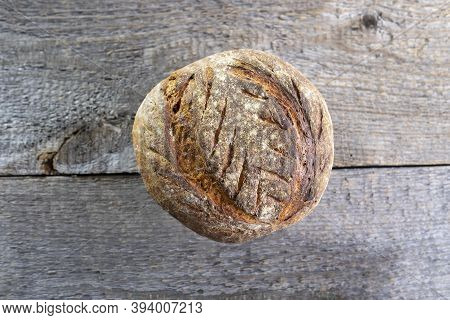 Homemade Sourdough Bread With Crisp Crust On Rough Board Background. Copy Space.