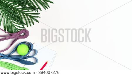 White Background And Resistance Loop For Exercise, Notebook For Workout Plan And Results, Top View.