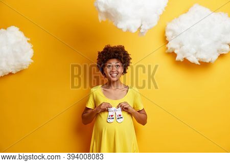 Positive Afro American Pregnant Woman Holds Small Baby Socks Over Pregnant Belly, Looks Hopefully Ab