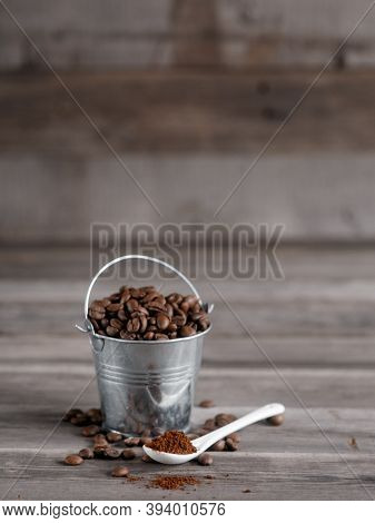 Arabica Coffee Beans In A Small Miniature Bucket. Ground Coffee In A White Ceramic Spoon On A Wooden