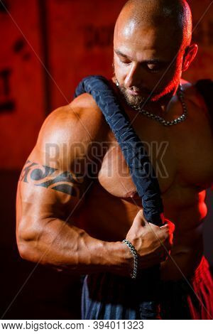 Sporty Handsome Strong Man Posing With Sports Rope On The Background Of The Gym. A Strong Bodybuilde