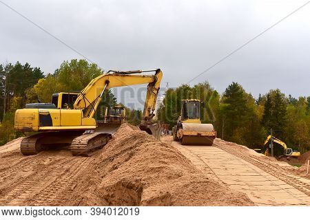 Excavator And Vibro Roller Soil Compactor At Road Construction And Bridge Projects In Forest Area. H