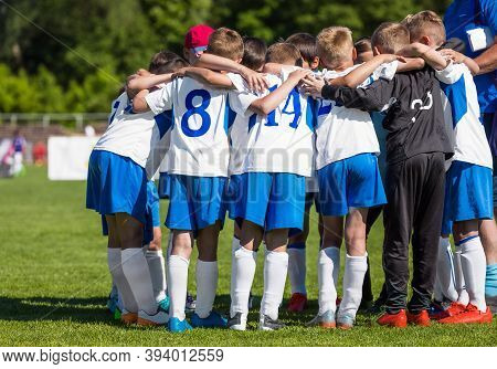 Coach With Children Soccer Team. Kids In White And Blue Soccer Uniforms Huddling In A Team. Boys Mot