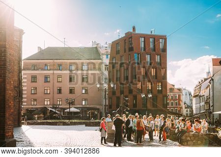 Riga, Latvia - June 9, 2019: Group Of Tourists On Excursions Near Statue Of The Bremen Town Musician