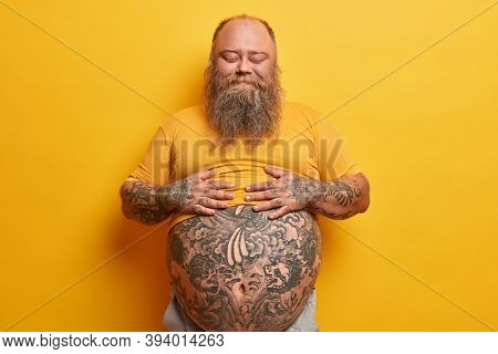 Pleased Stout Man Keeps Hands On Belly, Feels Satiety After Eating Delicious Dinner, Stands With Eye