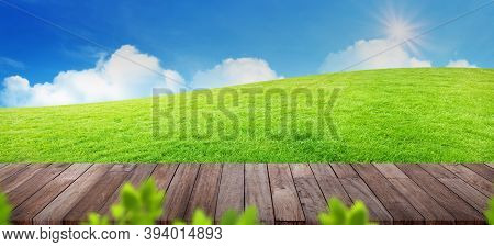 Wooden Table Top With Blurry Image Of Green Grass Meadow Field With White Clouds And Blue Sky In Bac