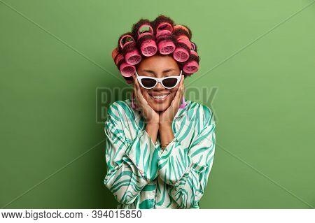 Joyful Dark Skinned Woman Touches Cheeks, Stands With Eyes Closed, Feels Pleasure, Wears Sunglasses,