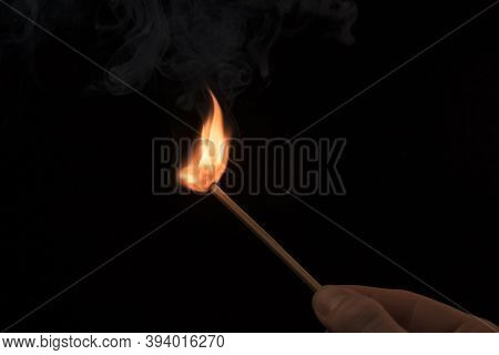 Hand Holding A Lighted Match With Fire Flame And Smoke On A Black Background.