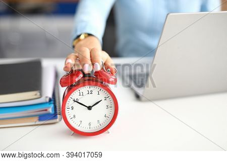 Womans Hand Lies On Red Alarm Clock Notebooks And Laptop Lie Next To It. How To Deal With Stress Whe