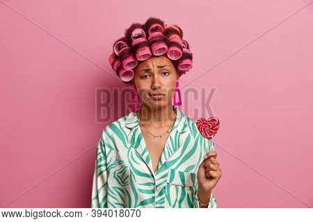 Sad Young Woman Gets Hair Permed, Looks Unhappily At Camera, Wears Hair Rollers, Dressed In Casual C