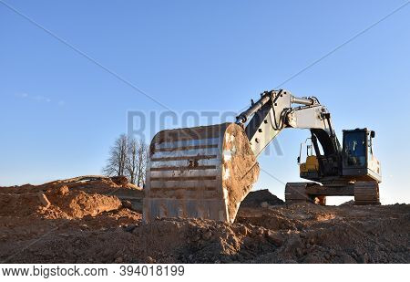 Excavator Working On Earthmoving At Open Pit Mining. Yellow Backhoe Digs Sand And Gravel In Quarry.