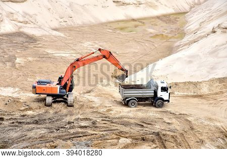 Excavator Load The Sand To The Heavy Dump Truck In The Open-pit. Heavy Machinery Working In The Mini