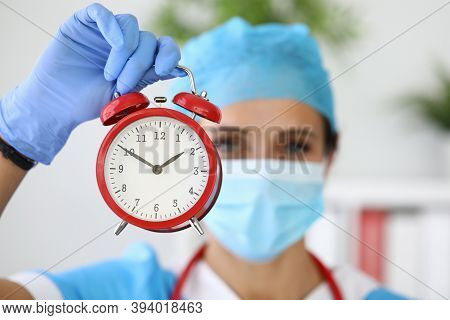 Doctor In Medical Protective Mask Holds Red Alarm Clock In His Hands. Health Insurance And Insured E