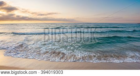 Sunrise At The Sea. Beautiful Summer Landscape On The Sandy Beach. Green Waves Rush On The Shore In