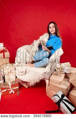 A Girl In A Blue Sweater Reads A Book On An Armchair. New Year Gifts