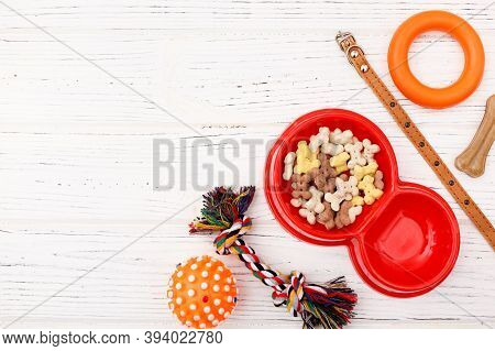 Set Of Accessories For The Dog On Wooden White Background. Red Bowl, Collar, Ball, Goodies. Caring C