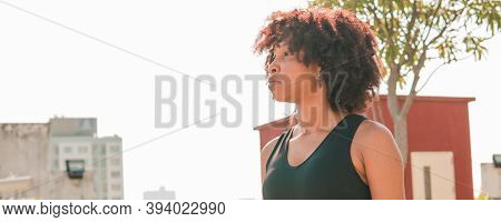 Young African American Woman Looking Far Distance Into The Skyline Buildings At Rooftops. Female Ath