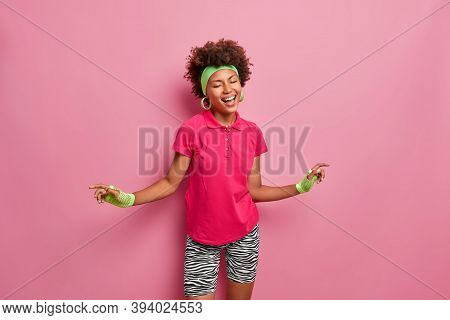 Happy Emotions And Lifestyle Concept. Cheerful Dark Skinned Sporty Woman Dances With Joy, Dressed In