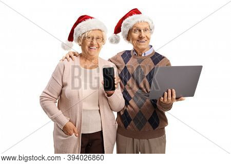 Cheerful elderly man and woman with christmas hats holding laptop computer and a smartphone isolated on white background