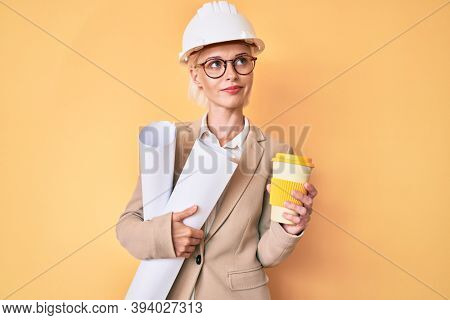 Young blonde woman with tattoo holding paper blueprints drinking take away cup of coffee smiling looking to the side and staring away thinking.