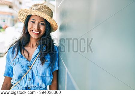 Young beautiful indian woman wearing summer hat. Leaning on the wall smiling happy at the city.