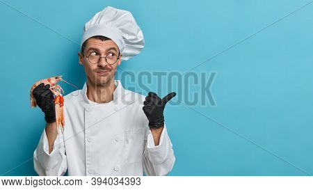 Professional Cook Holds Boiled Crayfish, Wears Uniform, Points Aside On Copy Space Against Blue Back