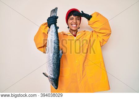 Beautiful brunettte fisher woman wearing raincoat holding fresh salmon stressed and frustrated with hand on head, surprised and angry face