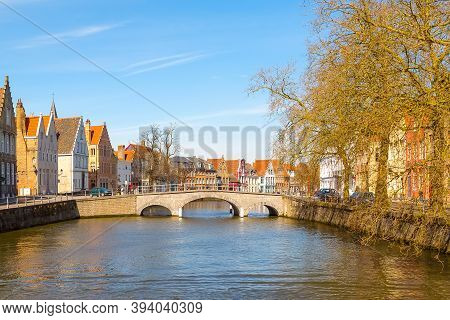 Bruges, Belgium - April 10, 2016: Panorama With Canal, Bridge And Colorful Traditional Houses Agains