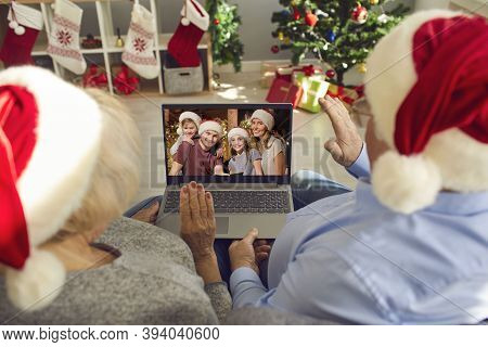 Happy Grandparents In Santa Hats Video Calling Their Family On Christmas Holidays In Lockdown