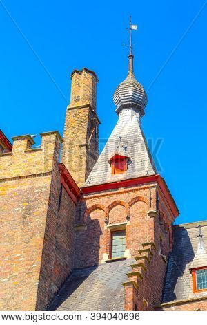 Bruges, Belgium Traditional Close-up Medieval Brick House Exterior Tower Against Blue Sky In Belgian