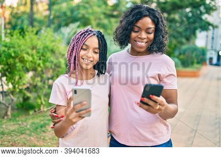 African american mother and daugther hugging and using smartphone at the park.